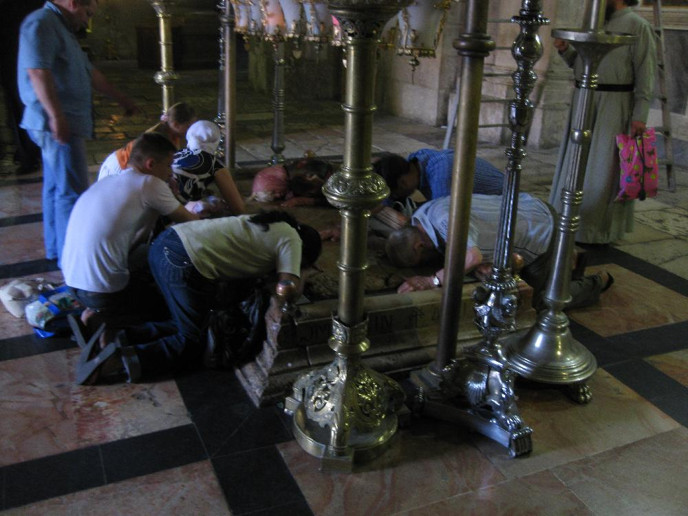 Christians kissing the tomb of Jesus